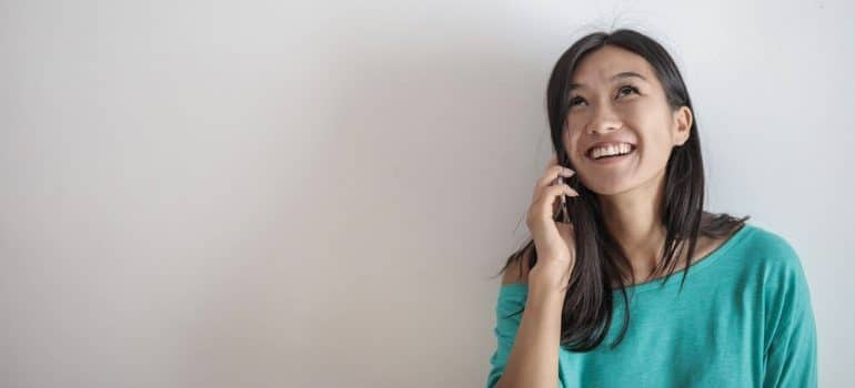 Woman talking on the phone with long distance movers in Maryland.