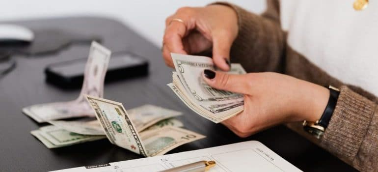 person with dollar bills in hands