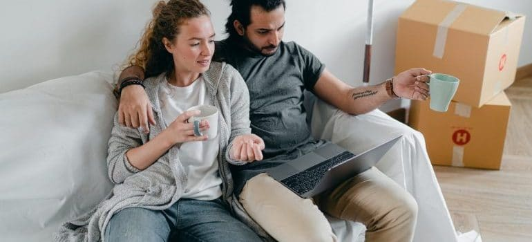 couple looking for Oregon long distance moving companies on a laptop while drinking tea in their packed living-room