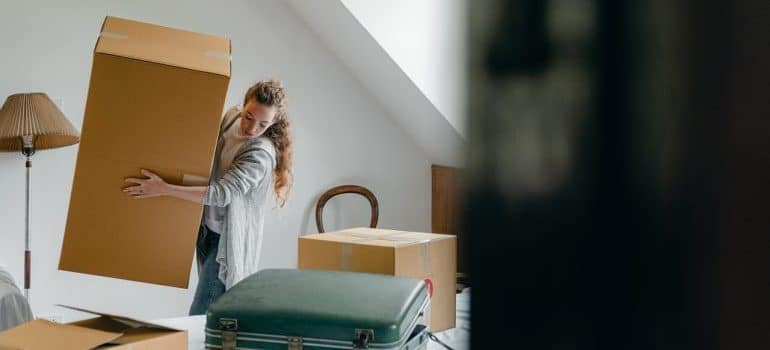a girl handling a moving box, representing arizona long distance movers