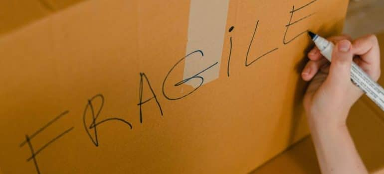 crop-person-packing-box-with-fragile-items