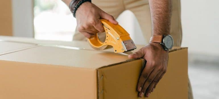 a person taping a moving box, representing alaska long distance movers