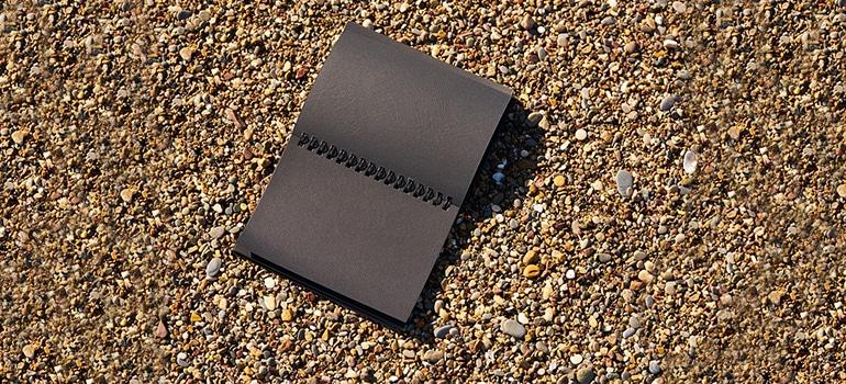 a black notebook on a beach