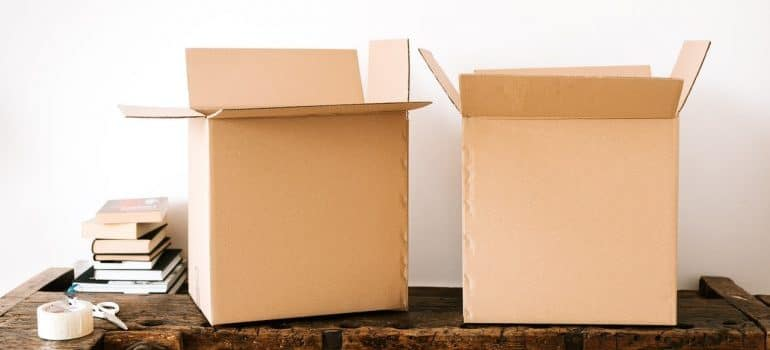 Two boxes on a wooden table with a white background.