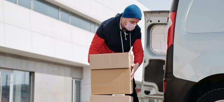 A man loading cardboard boxes into a white van.