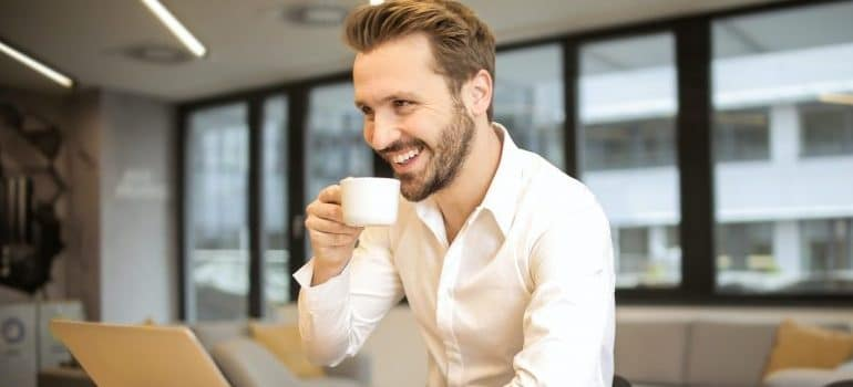 male working on the laptop, smiling, drinking coffee