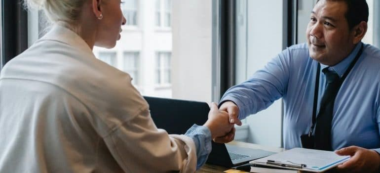 two people handshaking and talking how to maintain security during a long distance move
