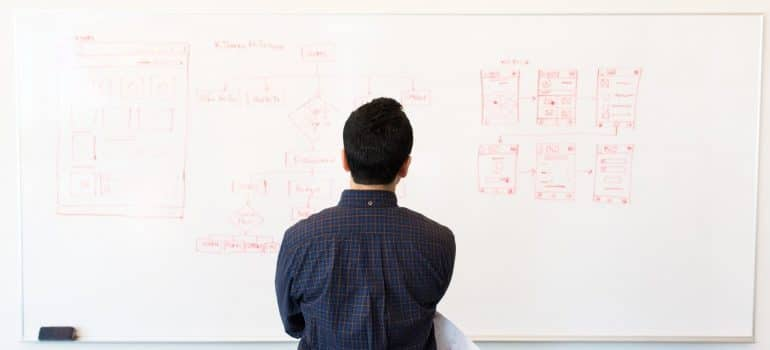 a man in a blue shirt looking at a whiteboard with plans written on it