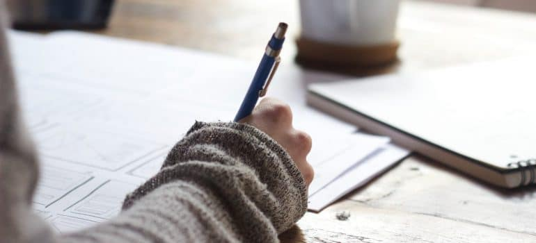 a woman wearing a green sweater writting her plans in a notebook
