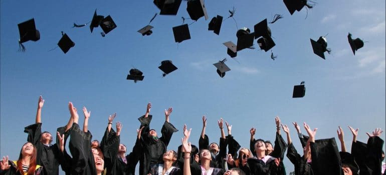 a group of college graduates throwing their hats in the air